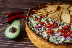 Australische Fleischtorte auf dem Tisch und Avocado, Paprika, Chips eine horizontale Draufsicht, rustikale Art Lizenzfreie Stockbilder