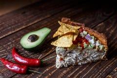 Australische Fleischtorte auf dem Tisch und Avocado, Paprika, Chips eine horizontale Draufsicht, rustikale Art Lizenzfreies Stockbild