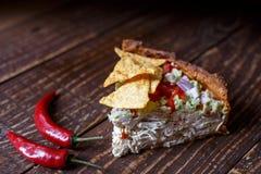 Australische Fleischtorte auf dem Tisch und Avocado, Paprika, Chips eine horizontale Draufsicht, rustikale Art Stockbild