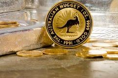 Australische Goldnugget-Münze mit Silberbarren im Hintergrund Stockbild