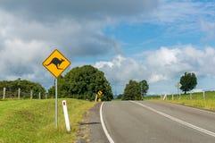 Australische Hinterlandstraße mit KänguruVerkehrsschild Lizenzfreie Stockbilder