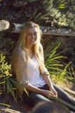 Australische Schönheit mit dem langen blonden Haar, das auf hölzernen Schritten sitzt Stockbilder