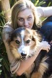 Australische Schönheit mit dem langen blonden Haar sitzt mit ihrem Colliehund Lizenzfreie Stockfotos