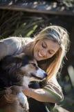 Australische Schoonheid met Lange Blonde Haarzitting met haar Collie Dog Stock Foto