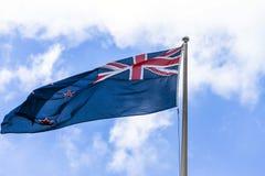 Australische vlag die tegen een blauwe hemel met witte wolken golven Stock Foto
