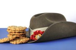 Australischer Armee Slouchhut und traditionelle Anzac-Kekse auf weißem und blauem Hintergrund Lizenzfreie Stockfotografie