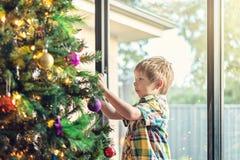 Australischer Junge, der Weihnachtsbaum verziert lizenzfreie stockfotos
