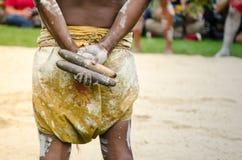 Australischer Ureinwohner, der traditionelle hölzerne Claves-Stoßinstrumente hält stockfotos