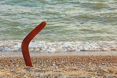 Australisk bumerang på den sandiga kustlinjen nära havsbränning Royaltyfria Bilder