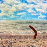 Australisk bumerang på den tropiska stranden mot havsvåg och blått Royaltyfri Foto