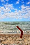 Australisk bumerang på den tropiska sundy stranden på havs- och himmelbaksida Arkivfoto