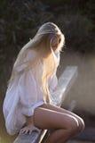 Australisk skönhet med långt blont hår ser ner med solen som strömmar till och med hår Royaltyfri Foto