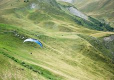 AUSTRIA, ALPS, May, 2016: The Paraglide Flying over the Fresh Green Mountain Meadow. The Paraglide Flying over the Mountain Meadow Stock Photos