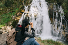 Austria. Bad Gastein. A girl with a camera. By the waterfall in the Alpine mountains Royalty Free Stock Photo