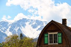 Austria Chalet with Alps. An Austrian chalet with windows and the Alps in the background Stock Photo