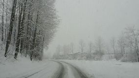 Austria. Driving shot, driver point-of-view. Footage driving on road during a snowfall stock footage