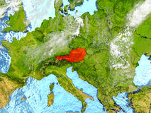 Austria on map with clouds. Austria in red on map with detailed landmass texture, realistic watery oceans and clouds above the surface. 3D illustration. Elements Royalty Free Stock Image