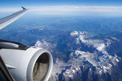 AUSTRIA - October 2016: The alps as seen from an airplane, wing view with plane turbine or engine Royalty Free Stock Photo