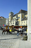 Austria, Vienna. Vienna, Austria - March 27th 2016: Unidentified people, horse drawn coach named Fiaker, Austria fountain and Scottish monastery on Freyung Royalty Free Stock Photography