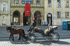 Austria, Vienna. Vienna, Austria - March 27th 2016: Unidentified tourists in horse drawn coach named Fiaker in front of Palais Ferstl on Freyung square Royalty Free Stock Images