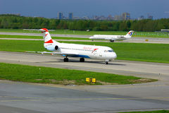 Austrian Airlines Fokker 100 and Severstal Canadair CRJ-200 aircrafts in Pulkovo International airport in Saint-Petersburg, Russia Royalty Free Stock Photography