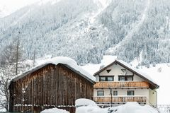 Austrian alpine village scenic landscape with small chalet and wooden barn ,pine forest trees and snow covered mountains on