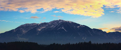 The Austrian alps With Orange Sky And Clouds. Above Them Royalty Free Stock Photos