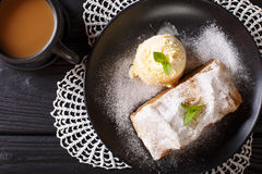Austrian apple strudel with vanilla ice cream and coffee with mi. Lk close-up on the table. horizontal view from above Stock Image