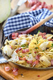 Austrian cuisine. Pasta with fried white cabbage and bacon, an Austrian specialty called 'Krautfleckerl', served in an iron frying pan Stock Photography