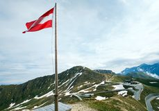 Austrian Flag above Alps mountain. Tranquil summer Alps mountain and Austrian Flag above Grossglockner High Alpine Road Stock Photos