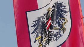 Austrian flag with coat of arms, national emblem waving in sky. Stock footage stock video footage