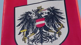 Austrian flag with coat of arms, national emblem waving in wind. Stock footage stock footage