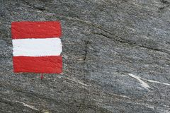 Austrian flag painted on rock. trail mark. natural full frame ba Stock Photo