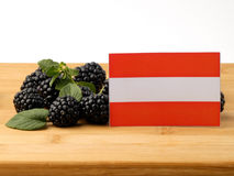 Austrian flag on a wooden panel with blackberries isolated on a Royalty Free Stock Photography