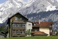 Austrian House in Mountains. Chalet accommodation in Austrian Tyrol with snowy mountain backdrop Stock Photo