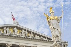 Austrian parlament with Athena statue and flag on cloudy sky used as background Stock Photos