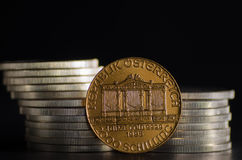 Austrian Philharmonic Gold Coin infront Silver Coins. On black background royalty free stock images