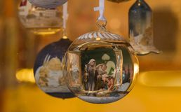 Christmas bauble with nativity scene. Austrian shop window with decorative Christmas glass boubles. This is finely decorated with a nativity scenes Stock Photography