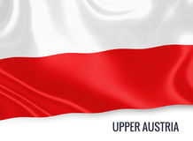 Austrian state Upper Austria flag. Austrian state Upper Austria flag waving on an isolated white background. State name is included below the flag. 3D rendering Royalty Free Stock Images