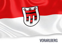 Austrian state Vorarlberg flag. Austrian state Vorarlberg flag waving on an isolated white background. State name is included below the flag. 3D rendering Royalty Free Stock Photos