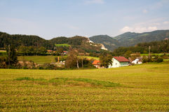 Austrian village. Field and mountains Stock Images