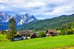 Austrian village among green meadows and Alps. Traditional Austrian village among meadows, fields and Alpine mountains. Knolls covered with green forests and Stock Photography