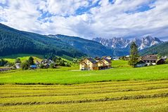Austrian village among meadows fields and Alpine. Mountains. Knolls covered with forests and blue sky with clouds. Picturesque summer landscape from Austria Stock Photography