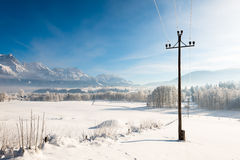 Austrian Winter Wonderland with mountains, fresh snow and haze in the sunlight Royalty Free Stock Photography