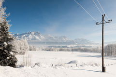 Austrian Winter Wonderland with mountains, a power pole, fresh snow and haze Stock Photos