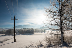 Austrian Winter Wonderland with mountains, a power pole in fresh snow and haze Royalty Free Stock Photo