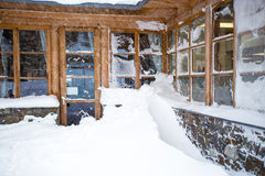 Austrian wooden house with big windows covered by snow at snowst. Classic Austrian wooden house with big windows covered by snow at snowstorm Royalty Free Stock Images