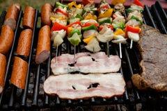 Auswahl des Fleisches grillend über den Kohlen mit würzigen Würsten, Speck und Hühneraufsteckspindeln Stockfoto