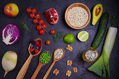 Auswahl des gesunden Lebensmittels Lebensmittelhintergrund: Quinoa, Granatapfel, Kalk, grüne Erbsen, Beeren, Avocado, Nüsse und O Stockbild