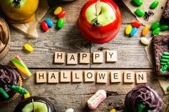 Auswahl von Halloween-Parteibonbons - Schokoladenkuchen, Karamelläpfel, kleine Kuchen, Schokoladencreme, Süßigkeiten lizenzfreie stockfotografie